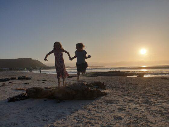 2 girls jumping on a beach