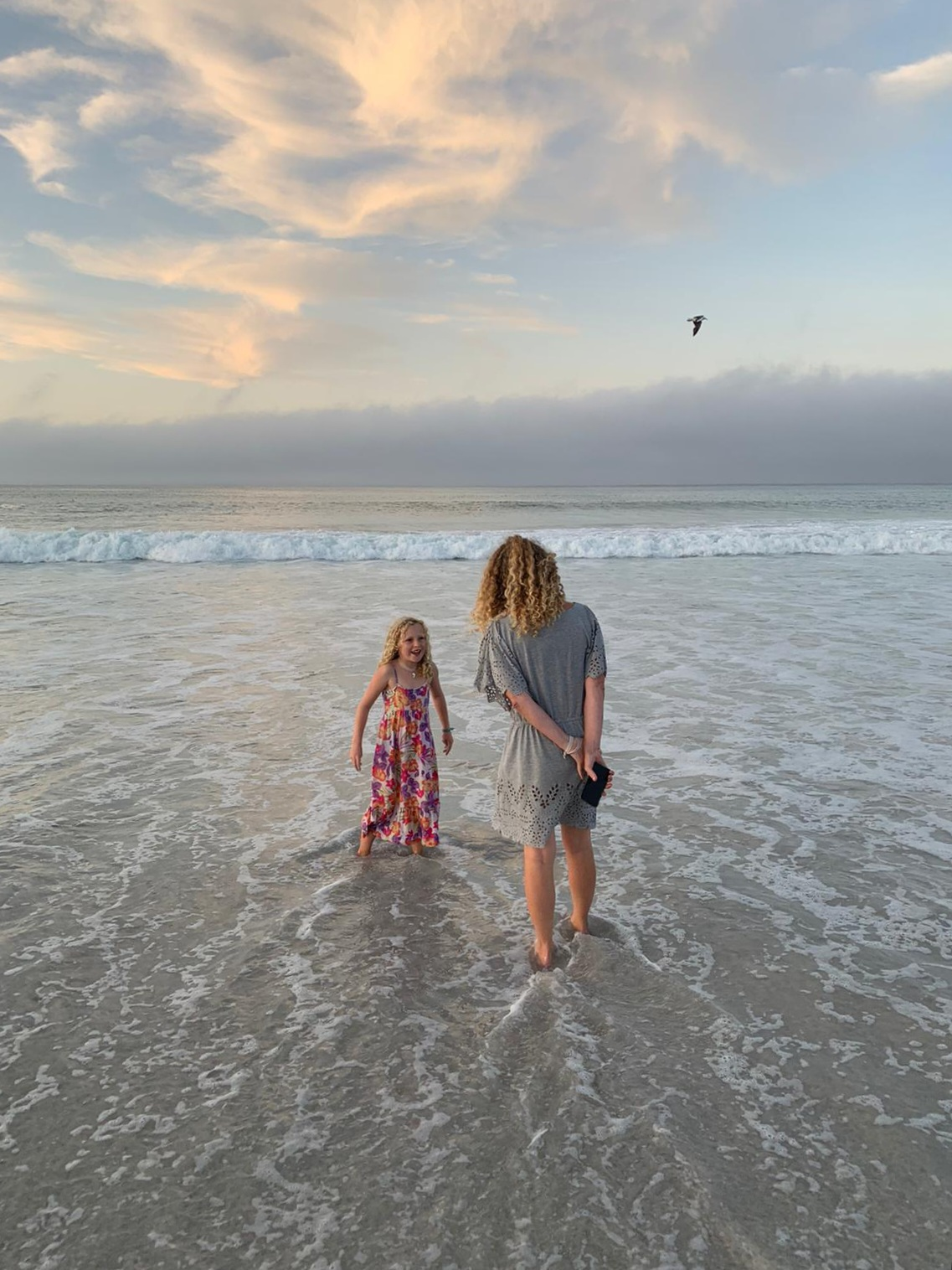 mom daughter and gull in the ocean shallows
