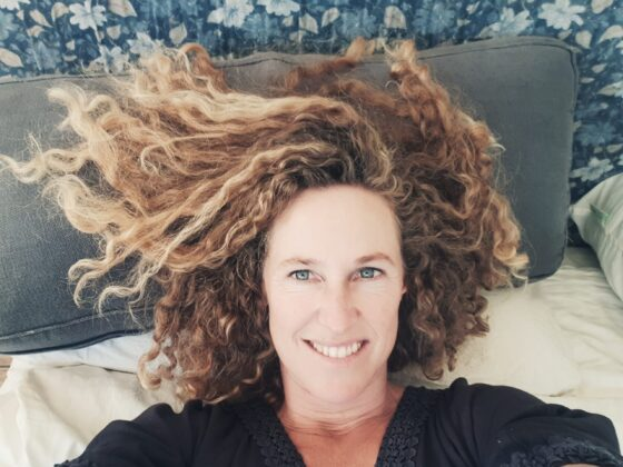 smiling curly woman against blue pillows