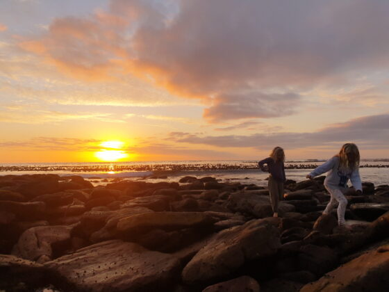 girls on rocks at sunset next to the sea