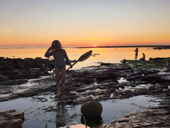 girl with paddle on seaside rocks at sunset
