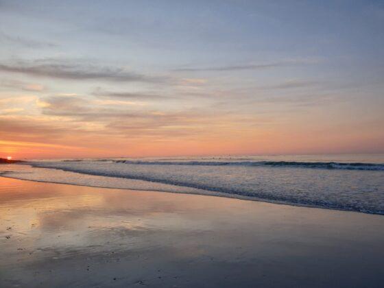 peachy sunset over the reflective beach