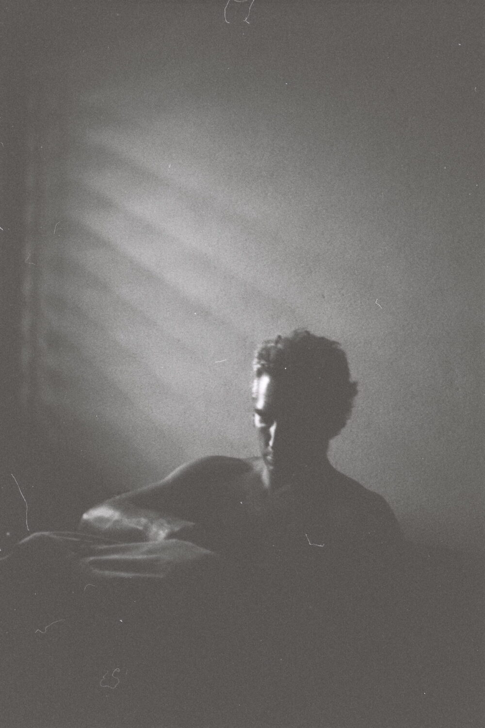 black and white image of man sewing