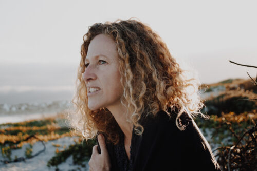 curly haired woman sitting on the beach