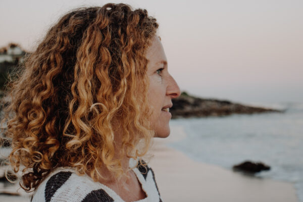 curly haired las in profile on beach