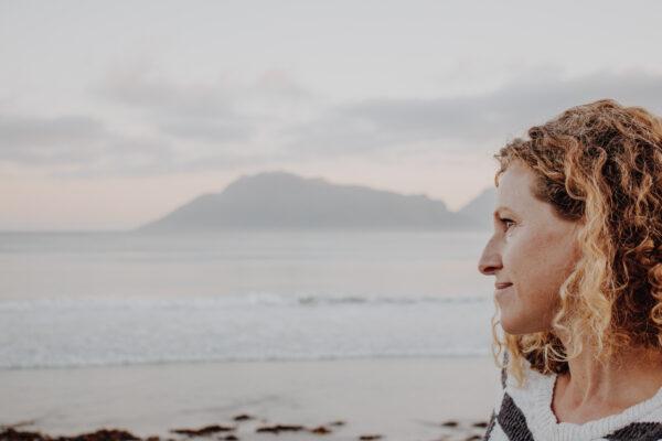 calm woman on the beach against dusky colours