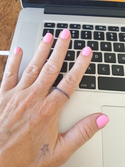 laptop and hand with pink nail polish