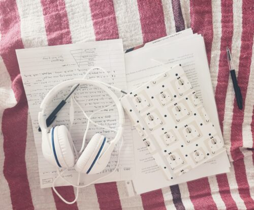 earphones notebook notes and pens