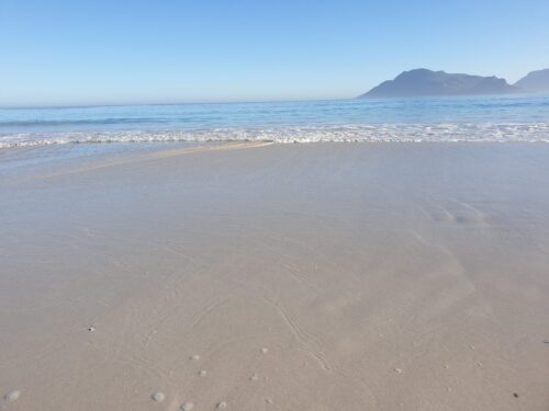 hazy blue sky and sea with sand in the forground