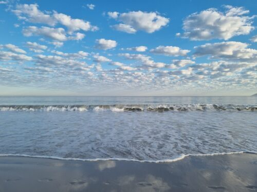 breaking wave beneath a cotton cloudy sky